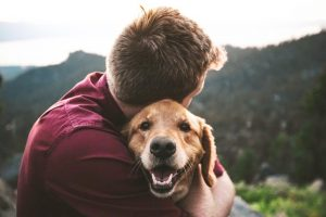 Dog and man hugging.